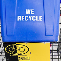 We Recycle! A blue recycling bin sits atop a yellow Bike Share bicycle--the epitome of urban environmentalism.