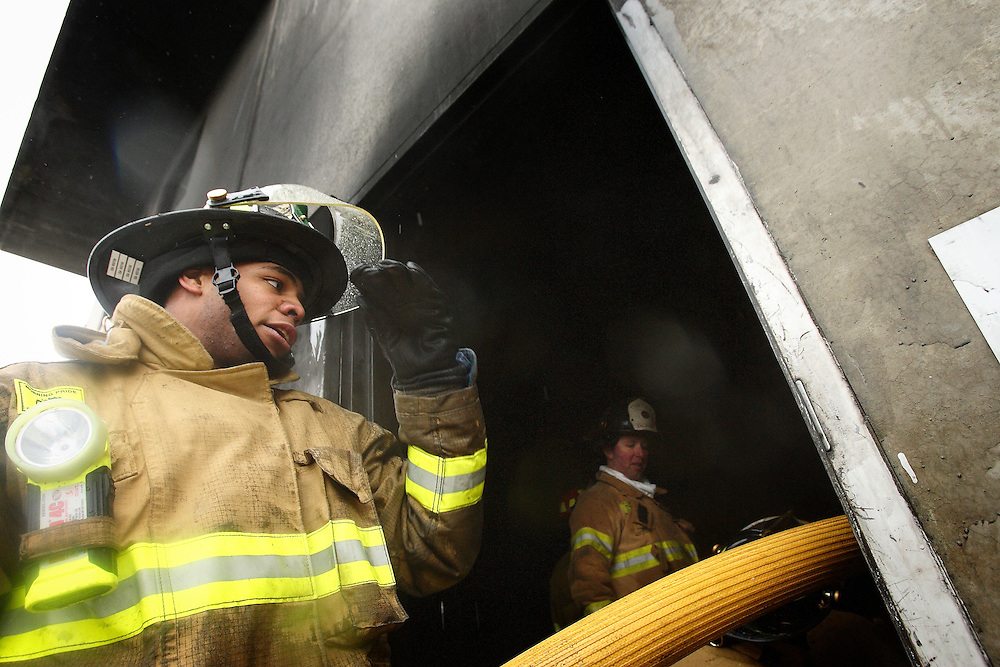 JEROME A. POLLOS/Press..Josh Hoston adjusts his visor after carrying in a fire hose to a training facility. Hoston is the first African-American firefighter hired by the Coeur d'Alene Fire Department.