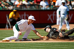 OAKLAND, CA - AUGUST 25: Mike Yastrzemski #5 of the San Francisco Giants is tagged out attempting to steal third base by Matt Chapman #26 of the Oakland Athletics during the seventh inning at the RingCentral Coliseum on August 25, 2019 in Oakland, California. The San Francisco Giants defeated the Oakland Athletics 5-4. Teams are wearing special color schemed uniforms with players choosing nicknames to display for Players' Weekend. (Photo by Jason O. Watson/Getty Images) *** Local Caption *** Mike Yastrzemski; Matt Chapman