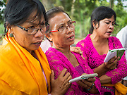 13 JULY 2016 - UBUD, BALI, INDONESIA: Women pray while a person's remains are cremated during the mass cremation in Ubud. Local people in Ubud exhumed the remains of family members and burned their remains in a mass cremation ceremony Wednesday. Almost 100 people will be cremated and laid to rest in the largest mass cremation in Bali in years this week. Most of the people on Bali are Hindus. Traditional cremations in Bali are very expensive, so communities usually hold one mass cremation approximately every five years. The cremation in Ubud will conclude Saturday, with a large community ceremony.      PHOTO BY JACK KURTZ
