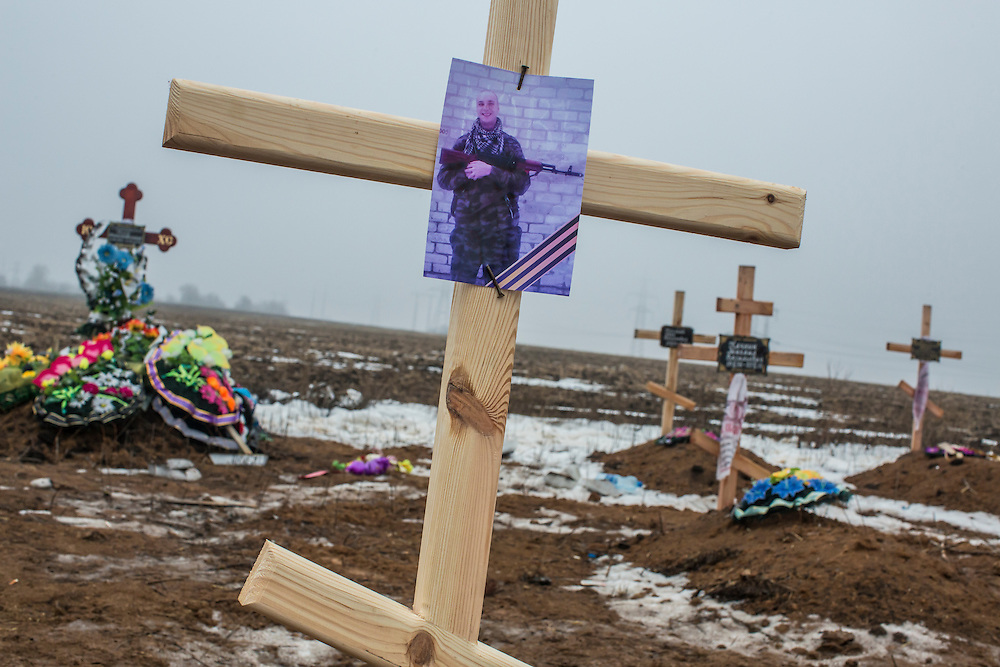 DONETSK, UKRAINE - JANUARY 30, 2015: A grave at Yuzhnaya Cemetery is marked only by a photo of a man with a gun and a St. George's ribbon, a symbol of pro-Russia rebels, in Donetsk, Ukraine. At least seven people were killed in two shelling incidents in Donetsk today, the deadliest day for civilians in more than a week, as peace talks in the Belarussian capital of Minsk were postponed. CREDIT: Brendan Hoffman for The New York Times