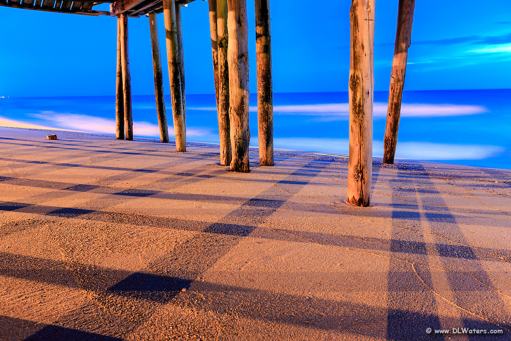 Shadows criss cross the beach under Avalon Fishing Pier on the Outer Banks at twilight.