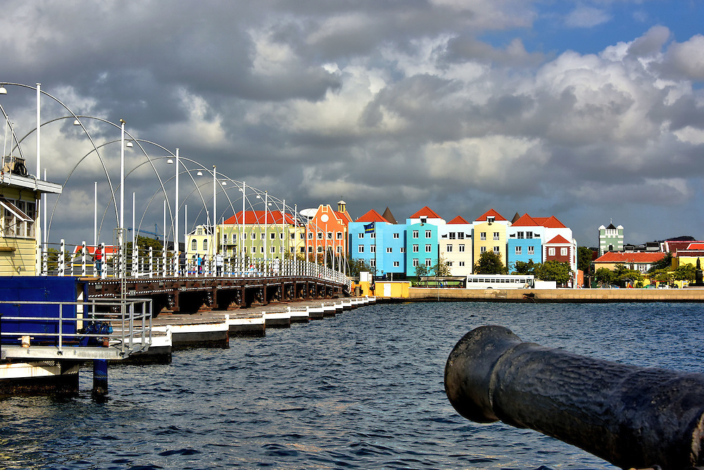 """Introduction to Capital City of Willemstad, Curaçao <br /> The initial inhabitants were the Caiquetío, an Arawak Indian tribe. Soon after the Spanish arrived in 1499, they named it Curaçao because they believed the island """"cured"""" sailors of scurvy. The Dutch conquered it in 1634. Today, Willemstad has a population of about 150,000 people and is the capital of this constituent country of the Kingdom of the Netherlands. The entire city is a UNESCO World Heritage Site. In the foreground is a late 18th century cast iron cannon. The 24 pounder next to the Queen Emma Bridge points across St. Anna Bay towards Otrobanda."""