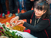 12 OCTOBER 2104 - BANG BUA THONG, NONTHABURI, THAILAND: A woman pours scented water over the hand of Apiwan Wiriyachai on the first day of his funeral rites at Wat Bang Phia in Bang Bua Thong, a Bangkok suburb, Sunday. Apiwan was a prominent Red Shirt leader, member of the Pheu Thai Party of former Prime Minister Yingluck Shinawatra, and a member of the Thai parliament. The military government that deposed the elected government in May, 2014, charged Apiwan with Lese Majeste for allegedly insulting the Thai Monarchy. Rather than face the charges, Apiwan fled Thailand to the Philippines. He died of a lung infection in the Philippines on Oct. 6. The military government gave his family permission to bring him back to Thailand for the funeral. He will be cremated later in October. The first day of the funeral rites Sunday drew tens of thousands of Red Shirts and their supporters, in the first Red Shirt gathering since the coup.    PHOTO BY JACK KURTZ