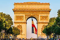 arc of triumph with the french flag floating in the city of Paris in france