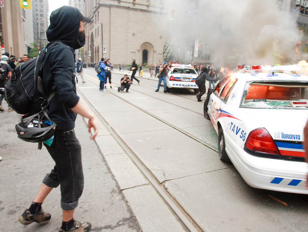Protesters smash police vehicles in the Toronto's downtown core June 26, 2010 after a small group of anarchists broke from the main anti G20 demonstration and began a destructive march through the downtown.<br /> AFP/GEOFF ROBINS/STR
