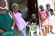 28 September 2011, Angola.  Ilumba Vocational Centre, Suburb Alvalade, LUNADA. The Ilumba Centre is a vocational training centre for woman and girls at risk. From left to right: Paola Garcia (30); Florinda Crispin (26); Suzette Concalvez (19); Martha Solange (23); Constantina Manuel (36). 1.Paola Garcia (30) – wearing green apron..Paola Garcia is at 30, the mother of 6 children. She was a stay-at-home mum when she thought of doing something to guarantee some level of financial independence and to set an example for her own children. ..She attended a course in 2005 and in 2006 was appointed as instruction assistant in the cooking class at the vocational centre, in the leafy suburb of Alvalade. ..Having completed only Grade 9, her hopes are that her children will do a lot better...2.Florinda Crispin (26) – pink and purple striped apron..Married, and the mother of 2 girls, 4 & 1 years old, this shy woman hopes to open a small confectionery business when she completes the course..3.Constantina Manuel (36) – Floral Apron ..Constantina got married at the age of 16, when her parents left Luanda to flee the war. Not long after their marriage, her husband suffered what sounds like stroke, and 20 years later he is still partially paralysed...Thrown into the role of primary breadwinner and forced to abandon school, Constantina started work at a small local restaurant, where she still works.  Now the mother of 6 (the oldest of which is 21) wants to improve her skills so that she can demand a higher salary, or even start her own business. ..4.Martha Solange (23) – Apron with apple on..Martha Solange is engaged to the father of her children, and will be getting married in November. She is mother to two daughters, 4 and 1 and is attending the centre to improve the traditional cooking that her mother taught her. ..5. Suzette Concalvez (19) - seated..Mother of 3-year old girl, completed grade 9, but wishes to complete school.Some of the courses they offer include Kindergarte