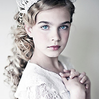 Headshot of young girl with  clear blue eyes and long blonde hair wearing white lace looking at camera