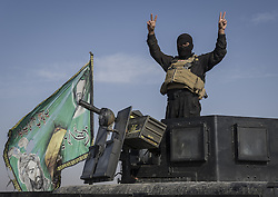 October 30, 2016 - Bartella, Nineveh Governorate, Iraq - Shia militia soldiers give the victory sign on the way to Bartella. Approximately 50,000 Iraqi security forces personnel, Kurdish Peshmerga fighters, Sunni Arab tribesmen and Shia militiamen are involved in the two-week offensive to drive ISIS militants out of their last major urban stronghold in the country. (Credit Image: © Berci Feher via ZUMA Wire)
