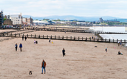 Portobello, Scotland, UK. 11 May 2020. Late afternoon views of popular Portobello beach and promenade. Despite occasional police patrols, the public were determined to relax and enjoy sitting in the sunshine. Iain Masterton/Alamy Live News