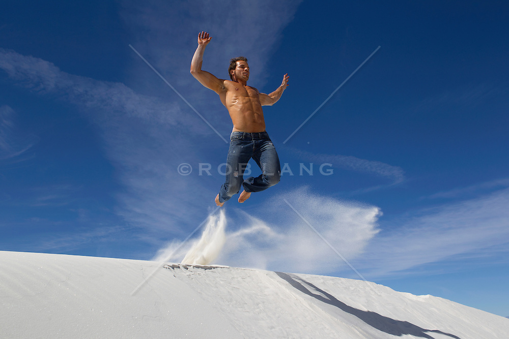 shirtless man in jeans jumping off a sand dune in White Sands National Park, New Mexico