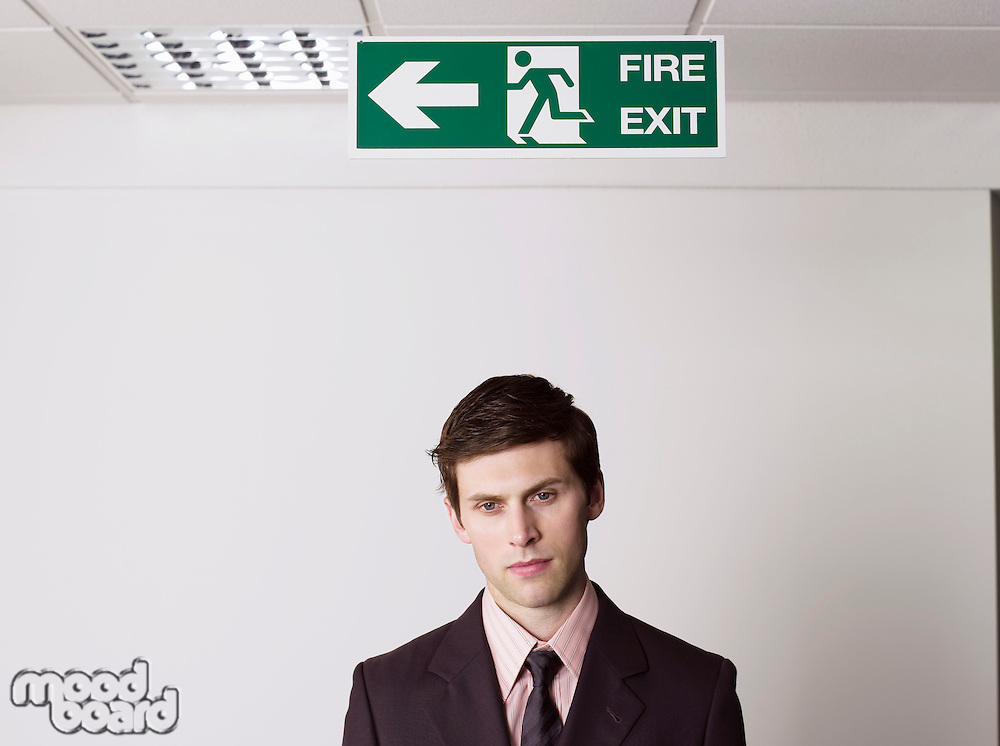Young businessman standing under exit sign