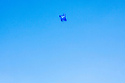 Blue plastic bag being wind swept across the big blue sky in London, United Kingdom.