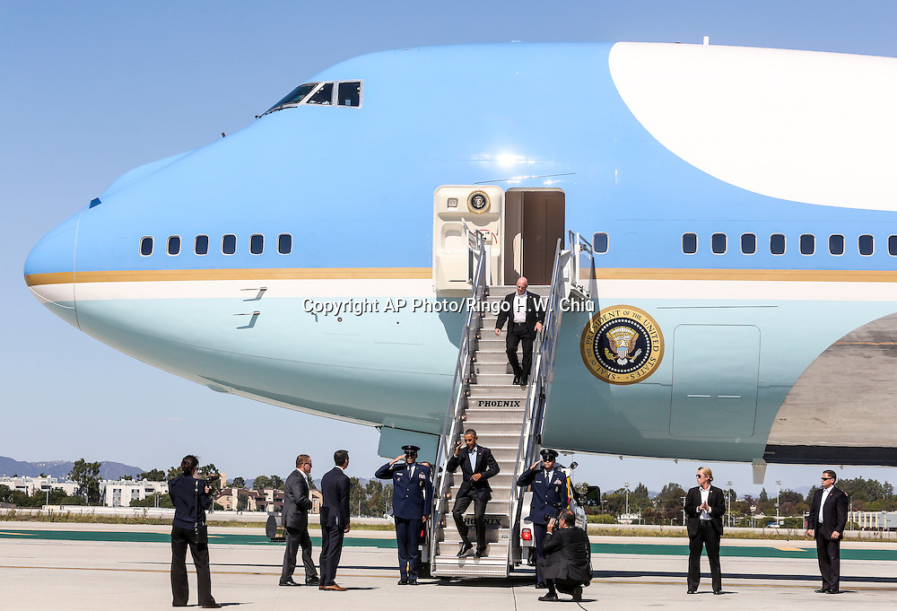 President Barack Obama salutes as he disembarks from Air Force One upon his arrival at Los Angeles International Airport in Los Angeles on Saturday, Oct. 10, 2015.  (AP Photo/Ringo H.W. Chiu)