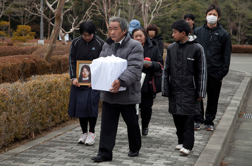The family of Katsumi Tsibdtda, 17, walks with his ashes after a cremation ceremony for him. His body was found after the earthquake and tsunami that hit the city of Rikuzen Takada, Japan, on 11 March 2011.