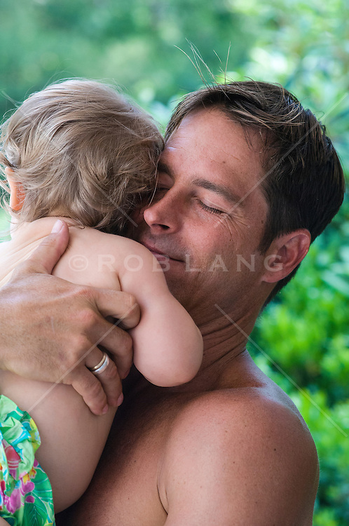 man holding a baby outdoors