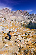Hiker under the Palisade peaks in Dusy Basin, Kings Canyon National Park, California USA