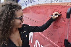 Iliana Barbosa (24) of Wyncote, PA signs a bus parked outside a Melanie Trump rally in Chester County, on Thursday.