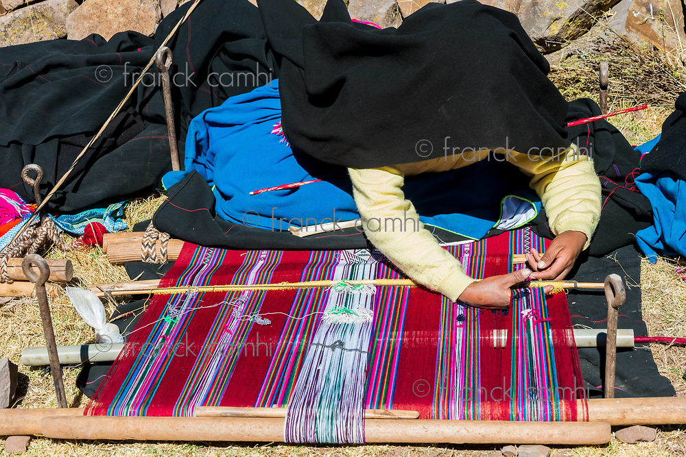 Puno, Peru - July 25, 2013: woman weaving in the peruvian Andes at Taquile Island on Puno Peru at july 25th, 2013.