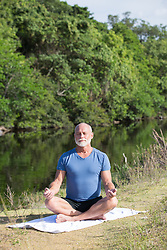 mature man meditating outdoors by a stream