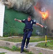 Logansport police officer Jason Shideler runs from the intense heat of the blaze at a home in the 500 block of Fitch Street Monday afternoon. Officers rushed to bring a disabled child from the adjoining home because of the intense heat. Photo by J. Kyle Keener / Pharos Tribune