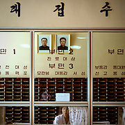 THE DEAR LEADERS ARE WATCHING YOU<br /> Anywhere you are in DPRK, you will see the portraits of the Dear Leaders. In the houses, in the offices, in the<br /> hospitals, in the subway, they never leave you!<br /> If you look carefully, you will see that they are the frames are leaning forward to avoid reflections that would<br /> make them difficult to see.<br /> Only the portraits of Kim Il Sung and Kim Jong Il can bee seen. Kim Jong Un has not yet portrait yet. They are<br /> sometimes accompanied by a portrait of Kim Jong Suk, Kim Il Sung's first wife, and the mother of Kim Jong Il.<br /> In this case they are dressed with military uniforms and caps.<br /> They are two versions, one with pictures from the 80's where the Leaders are very serious, one from the 90s<br /> where they smile. Some say they were the only people who smiled in North Korea.<br /> The portraits are so photshopped, in fact retouched by hand by north korean artists, that they look more ike<br /> paintings that pictures.<br /> The people who marry receive the two portraits and sometimes a third one showing Kim il Sung and Kim Jong Il<br /> chating with papers in the hands. This picture is really bad as it is taken with flash in a corridor office. When i<br /> asked my guide, he admitted this was not a perfect quality picture but it was the perfect illustration of the Dear<br /> Leaders working for the people, even when they were walking.<br /> When you ask north koreans if those portraits are not too much everywhere, they say that as they venerate the<br /> Leaders, it is a pleasure to see them all day long. My guide even noticed that many people have Jesus crucifix<br /> inside their bedrooms in western countries, for him, it was the same…<br /> The frames must always be clean, without fingers marks or dust for example. If you are caught not taking care<br /> of your portraits, you may have problems with the Party or even fined. I noticed that many portraits were dull<br /> because of the sun l