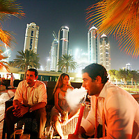 Hamza Abu Zanad, 27, from Jordan, right, smokes shisha with friends at an exclusive bar in Dubai. August 2008.