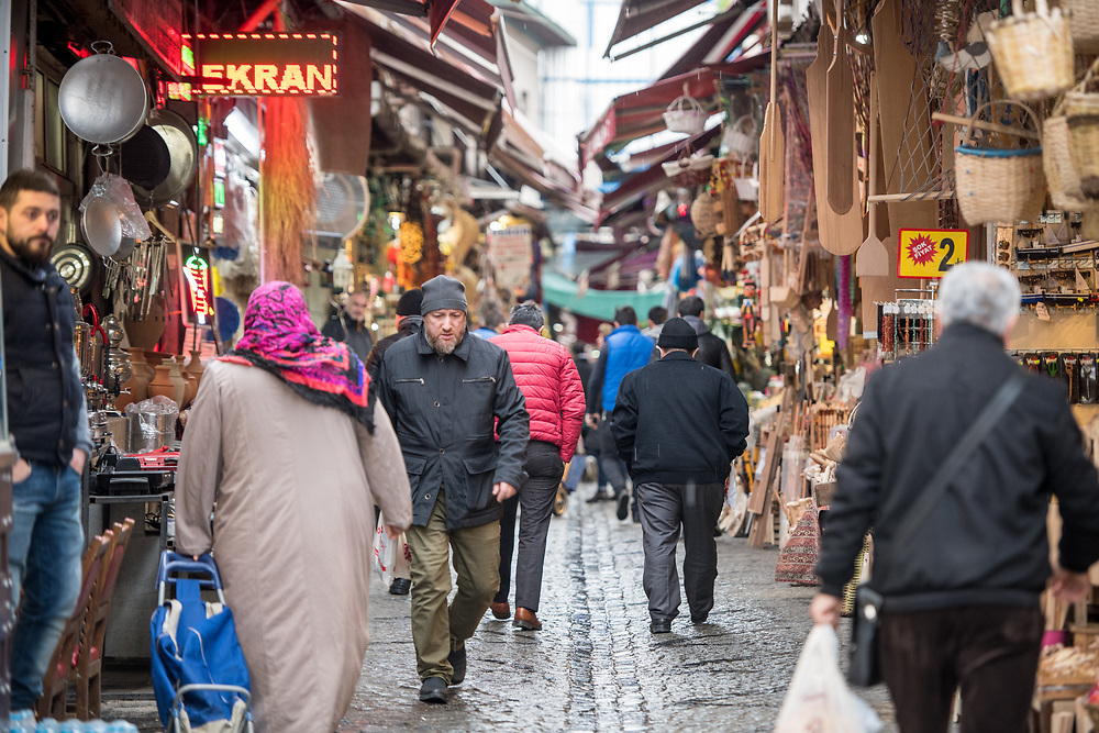 Shoppers walk along busy narrow street of outdoor marketplace selling various goods, Istanbul, Turkey