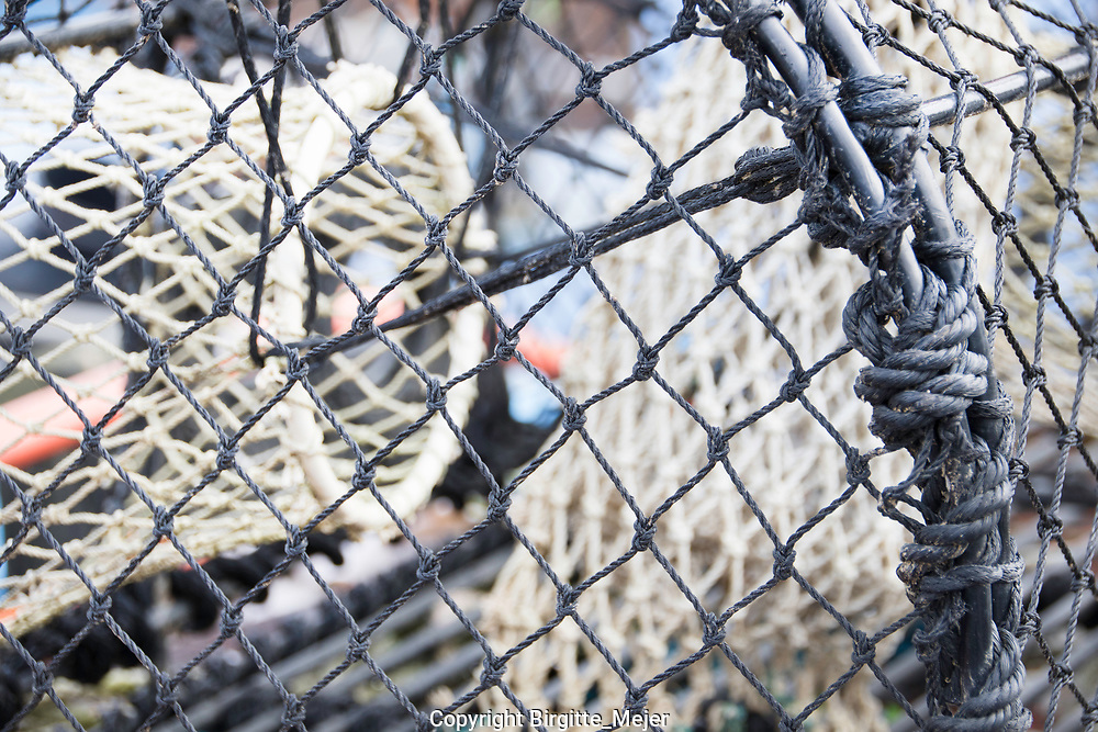Close up photography of the knots in a fish trap, fith other fish nets inside, blurred out.