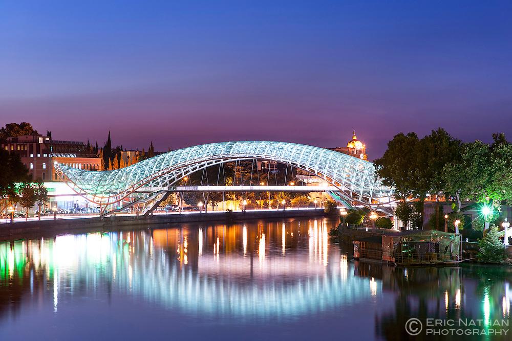 Dusk view of the Bridge of Peace, a pedestrian bridge spanning the Mtkvari River in Tbilisi, the capital of Georgia.