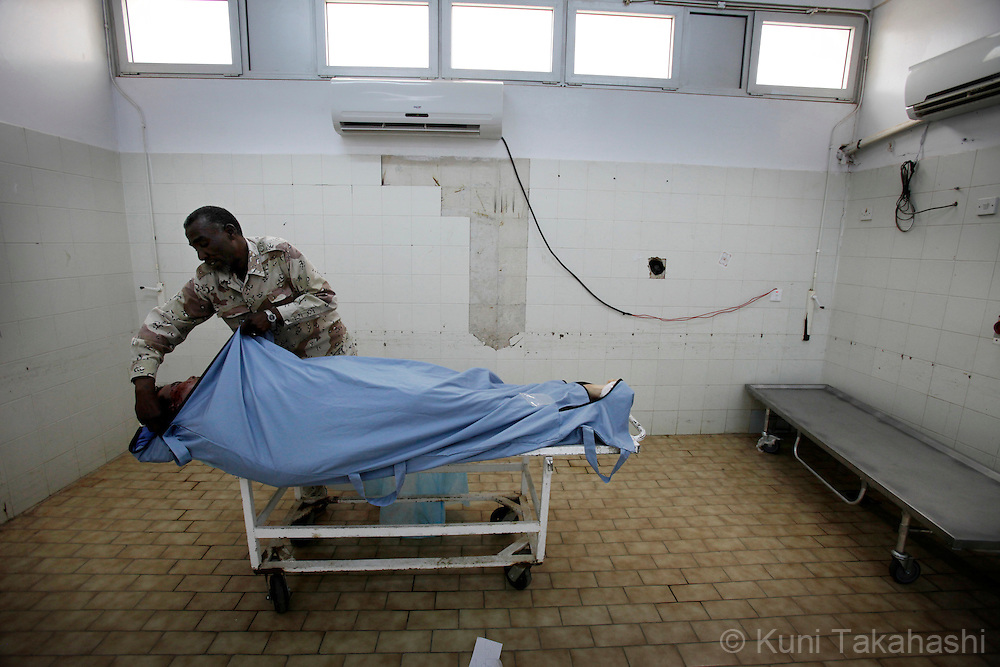 Hospital worker wraps a body of Ahmed Lagha, 18, in a morgue in Benghazi, Libya on May 22, 2011. Lagha was killed during a fight against Moammar Gadhafi's forces near Ajdabia.  In a boost to Libya's rebels, the European Union opened a diplomatic office Sunday in their eastern stronghold Benghazi and pledged support for a democratic Libya. Photo by Kuni Takahashi.