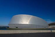 A panoramic shot of The Blue Planet Aquarium in Copenhagen set against a blue sky.