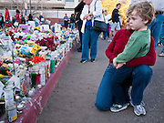 "15 JANUARY 2011 - TUCSON, AZ: A woman and her son look at the memorial on the lawn in front of the University Medical Center in Tucson, AZ, Saturday, January 15. The memorial has been growing since the mass shooting last week. Six people were killed and 14 injured in the shooting spree at a ""Congress on Your Corner"" event hosted by Congresswoman Gabrielle Giffords at a Safeway grocery store in north Tucson on January 8. Congresswoman Giffords, the intended target of the attack, was shot in the head and seriously injured in the attack. She is hospitalized at UMC. The alleged gunman, Jared Lee Loughner, was wrestled to the ground by bystanders when he stopped shooting to reload the Glock 19 semi-automatic pistol. Loughner is currently in federal custody at a medium security prison near Phoenix.  Photo by Jack Kurtz"