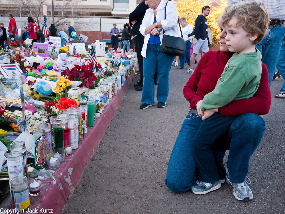 """15 JANUARY 2011 - TUCSON, AZ: A woman and her son look at the memorial on the lawn in front of the University Medical Center in Tucson, AZ, Saturday, January 15. The memorial has been growing since the mass shooting last week. Six people were killed and 14 injured in the shooting spree at a """"Congress on Your Corner"""" event hosted by Congresswoman Gabrielle Giffords at a Safeway grocery store in north Tucson on January 8. Congresswoman Giffords, the intended target of the attack, was shot in the head and seriously injured in the attack. She is hospitalized at UMC. The alleged gunman, Jared Lee Loughner, was wrestled to the ground by bystanders when he stopped shooting to reload the Glock 19 semi-automatic pistol. Loughner is currently in federal custody at a medium security prison near Phoenix.  Photo by Jack Kurtz"""