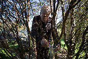 Tattoed hermit Tom Leppard replenishes bird seed for nearby beloved wildlife in trees near secret hideaway shelter on Skye