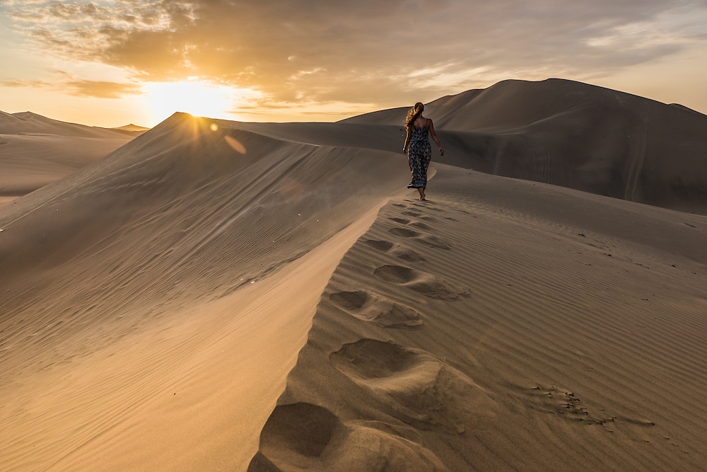 Woman walks on top of a sanddune at sunset near the town of Huacachina, Peru.