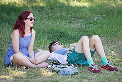 © Licensed to London News Pictures . 19/07/2013 . Suffolk , UK . A young couple shelters in the shade at The Latitude music and culture festival in Henham Park , Southwold . Photo credit : Joel Goodman/LNP