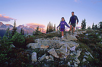 Dad walks with daughter on rocks in an alpine meadow during an evening hike on Whistler Mountain, BC, Canada.