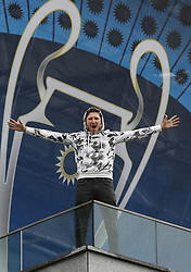 May 13, 2018 - Kiev, Ukraine - A man poses for a picture in front of NSC Olimpiyskiy covered with banners for the Champions League in Kyiv, Ukraine, May 13, 2018. Kyiv prepares to host UEFA Women's Champions League final between Wolfsburg and Lyon at Valeriy Lobanovskiy Dynamo Stadium on 24 May, 2018 and the UEFA Champions League final match between Real Madrid and  Liverpool at NSC Olimpiyskiy Stadium on Saturday 26 May, 2018. (Credit Image: © Sergii Kharchenko/NurPhoto via ZUMA Press)
