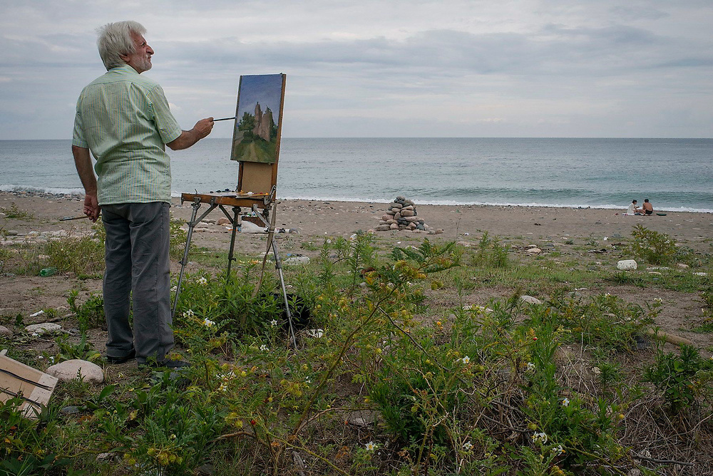 A local artist paints a wall (The Great Abkhaz wall) and landscape near the beach in Sukhumi, Abkhazia