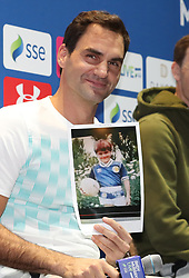 Roger Federer holds a photograph of himself aged 6 wearing a Scotland shirt in South Africa during a press conference ahead of the Andy Murray Live Event at the SSE Hydro, Glasgow.