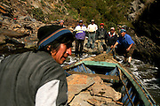 Members of a &quot;Lafquenche&quot; (People of the sea) community load a boat with stone. <br /> The Community of Mehuin, in southern Chile, have been struggling for more than ten years to prevent that CELCO (Arauco Cellulose), a major cellulose industry, builds a pipeline to throw away their industrial waste into the sea causing great impact in the ecosystem and their fishing and diving way of making a living.
