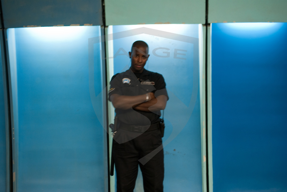 a police officer stands guard in the rio de janeiro subway system.  such improvements to public safety are on the rise as rio prepares for the 2016 olympics.