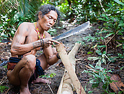 Mentawai indigenous man making a loincloth with machete (Indonesia).