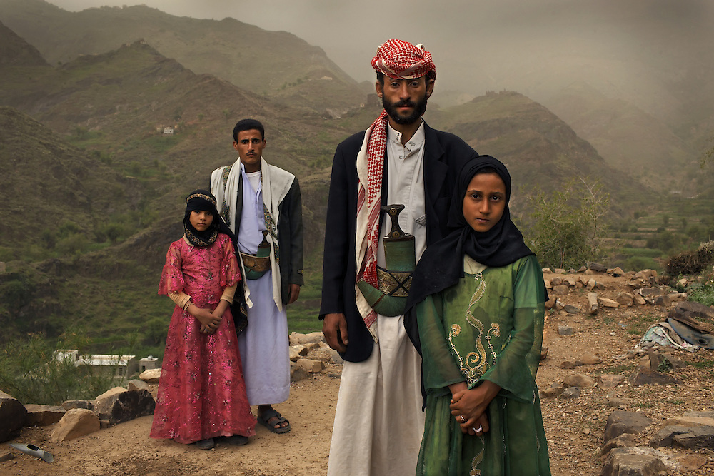 Tahani, 8, is seen with her husband Majed, 27, and her former classmate Ghada, 8, and her husband outside their home in Hajjah, Yemen, July 26, 2010.