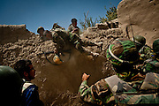 Afghan National Army soldiers hurl themselves over a wall to escape incoming fire from the Taliban.