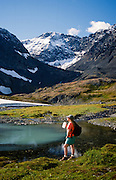 Alaska. Crow Pass. Chugach Mts. Hiker, Thalia Wilkinson enjoys the view of a small glacier lake. MRA