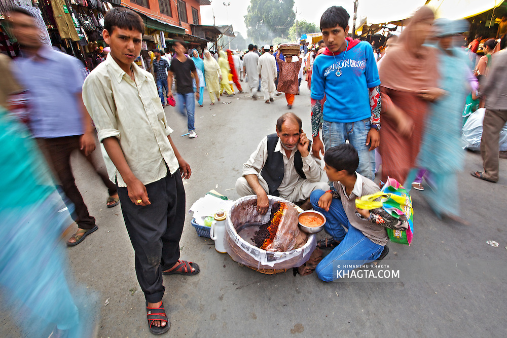 A vendor sells a local snack in the middle of the road to Hazratbal Shrine. <br /> <br /> Devotees converged for peace prayers at the famous Muslim shrine of Hazratbal to mark Meraj-ul-Alam festival in Srinagar, Prophet Mohammed's Moi-e-Muqaddas (Holy Relic) is displayed for public viewing on ten occasions in a year, which includes Meraj-ul Alam.