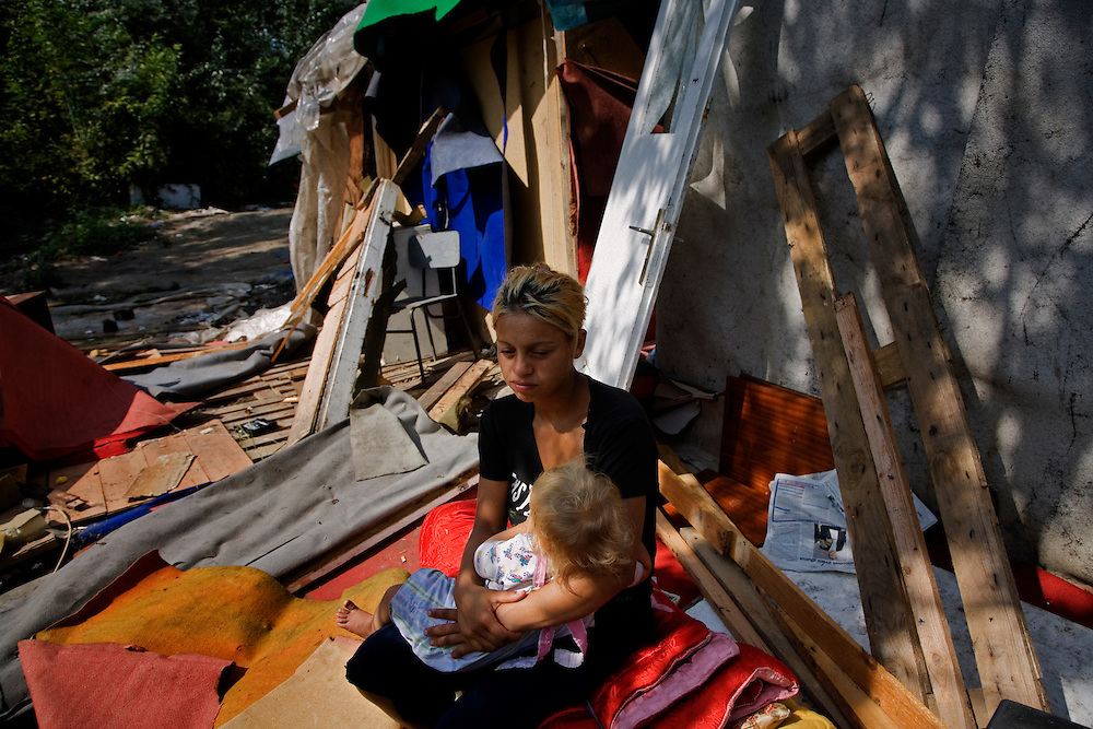 Elvis' 17 year old wife and their daughter sit in the rubble of their former home while waiting for government officials to sweep the Stara Gazela camp.