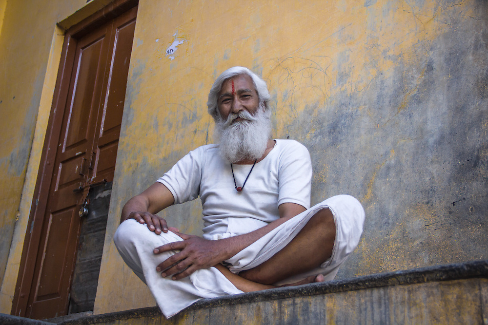 A friendly hindu man, dressed in white, sits on his doorstep in  Pushkar, India.
